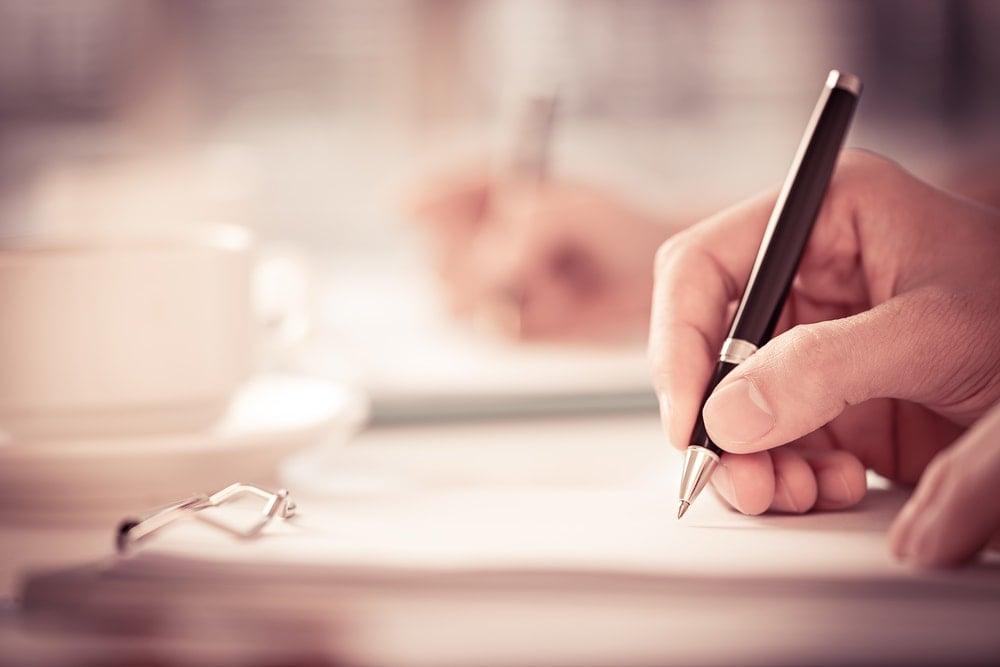 mão segurando caneta escrevendo