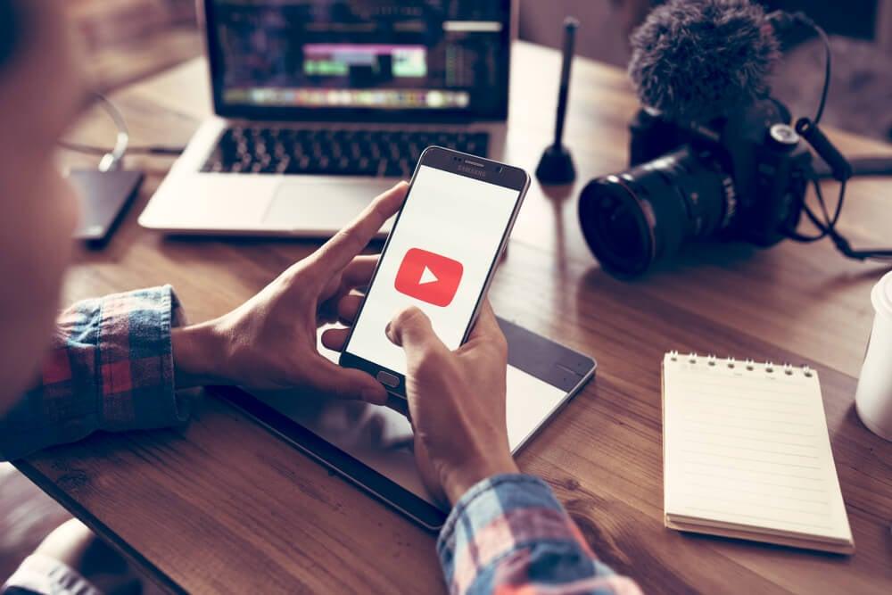 homem segurando smartphone com o icone da empresa youtube em mesa com bloco de notas laptop e camera fotografica