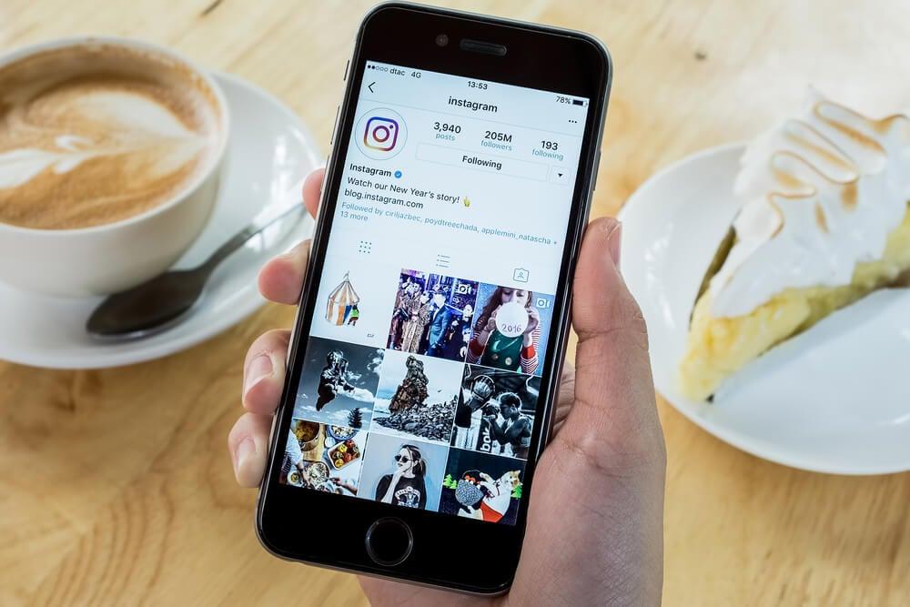 mao masculina segurando smartphone com perfil do aplicativo instagram em tela