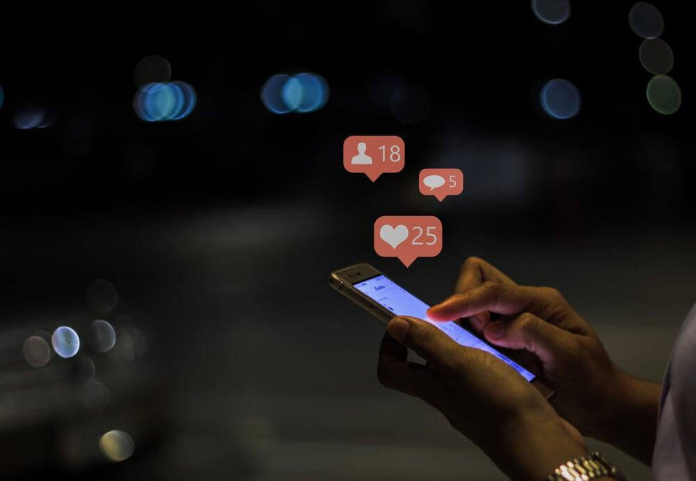 maos segurando smartphone com ilustraçoes de curtidasc ao lado