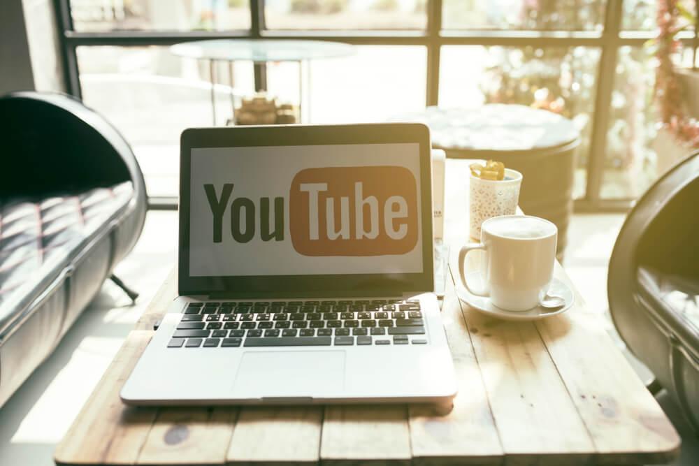 sala de estar com laptop em mesa de centro mostrando simbolo da empresa youtube