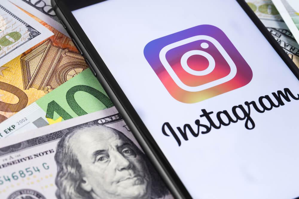tela de smartphone com icone do aplicativo instagram em tela  e notas de dinheiro ao fundo
