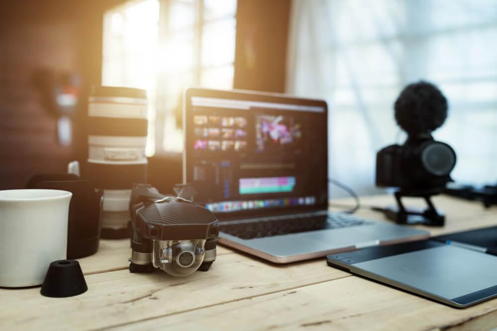 laptop com ediçao de video em tela sob mesa com materiais de video em sua volta