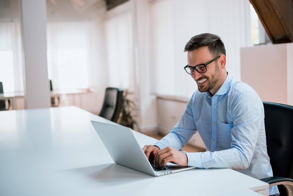 homem em escritorio sorrindo ao observar tela de laptop