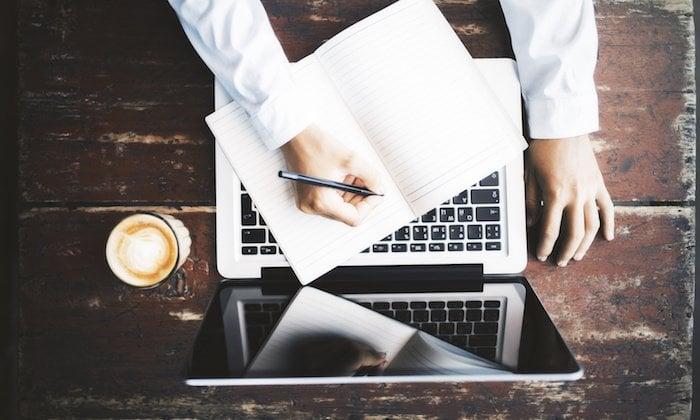 homem escrevendo em bloco de notas em frente a laptop sob mesa