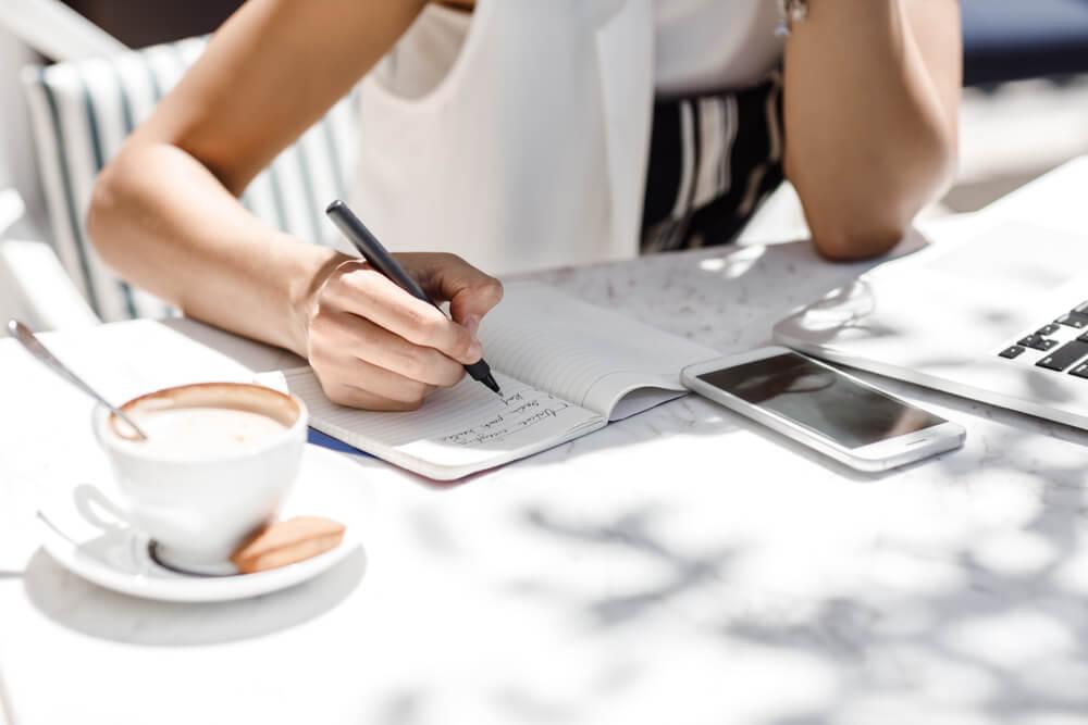 mulher escrevendo em bloco de notas em frente a laptop com xicara de cafe ao lado