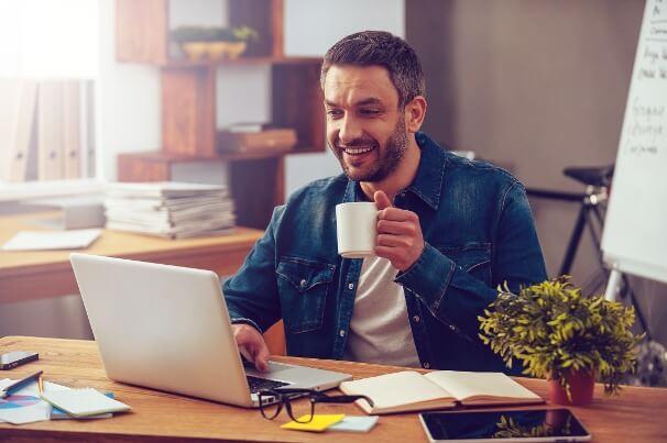 profissional da área digital com expressão feliz em frente a laptop