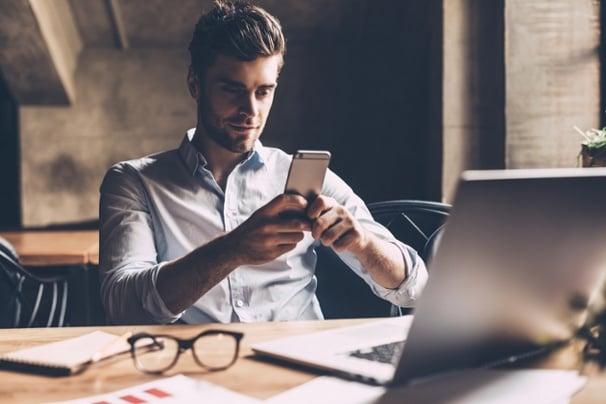 profissional digital acessando smartphone em frente a laptop