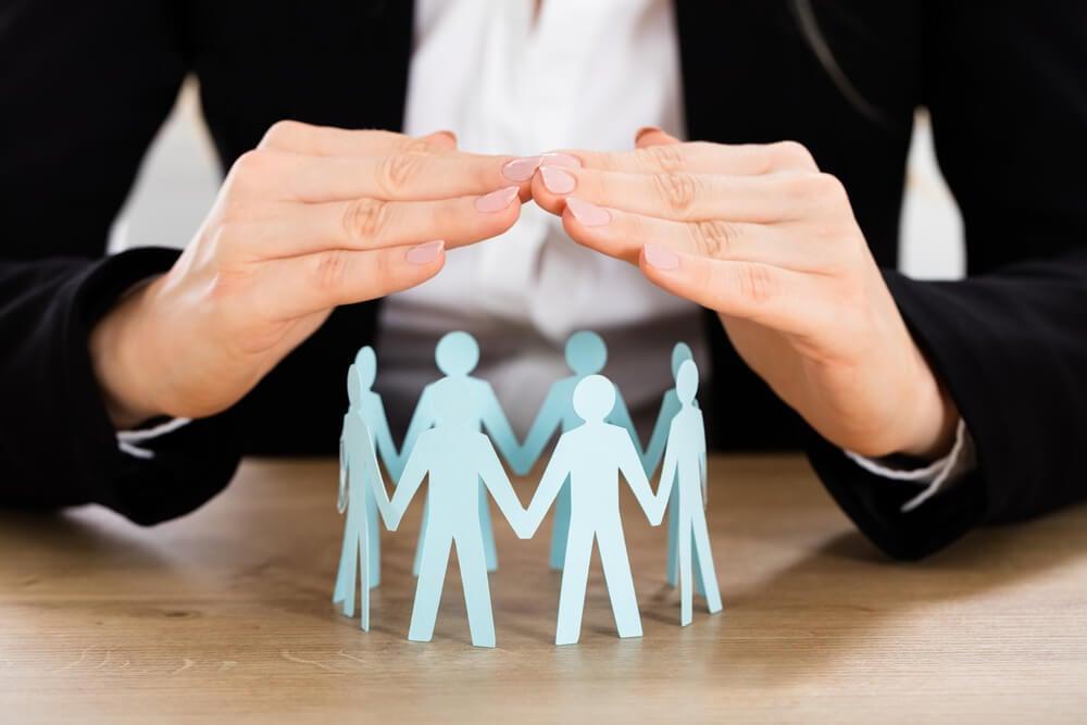 mãos protegendo representação de grupo de pessoas