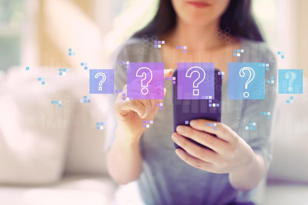 mulher acessando smartphone com símbolos de perguntas