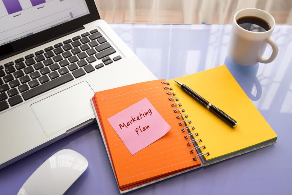 caderno em mesa junto de laptop com anotação do título plano de marketing
