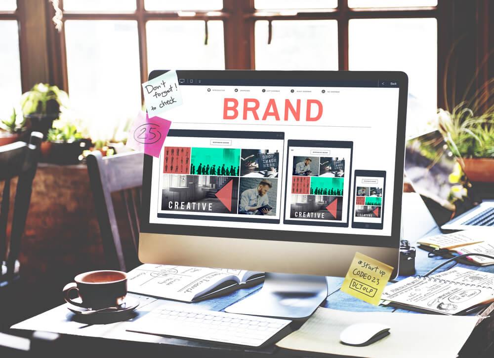 computador com anotações em mesa de escritório e marca na tela representando identidade visual