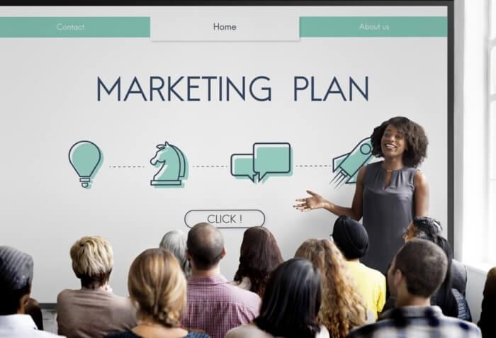 equipe em palestra dada por profissional sobre plano de marketing
