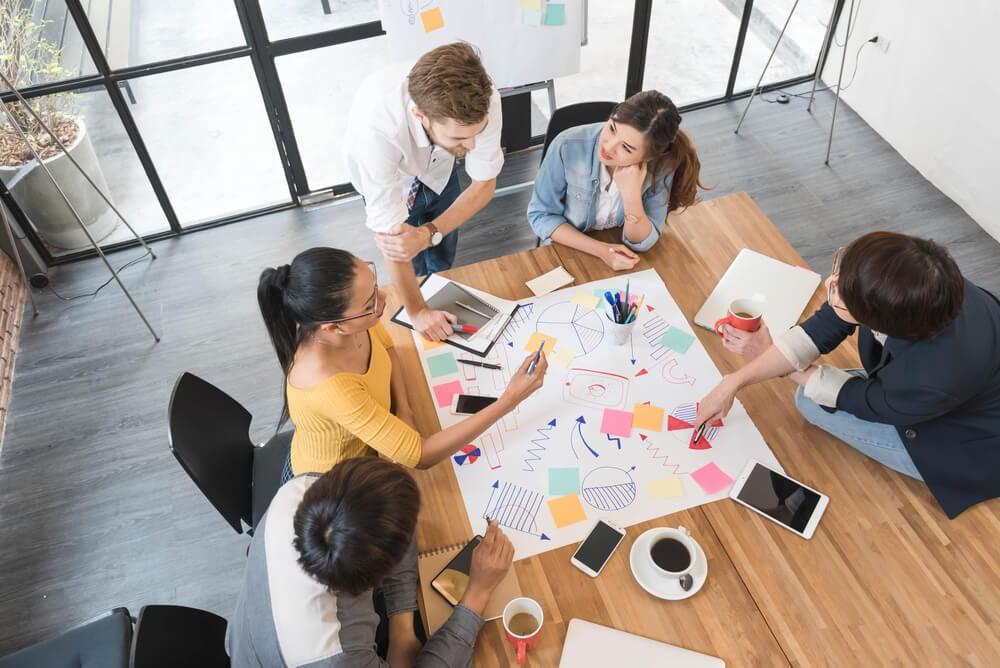equipe em processo de brainstorming em mesa de reuniões