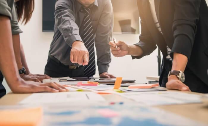 equipe empresarial em volta de mesa com papéis e dados importantes a construção de plano estratégico