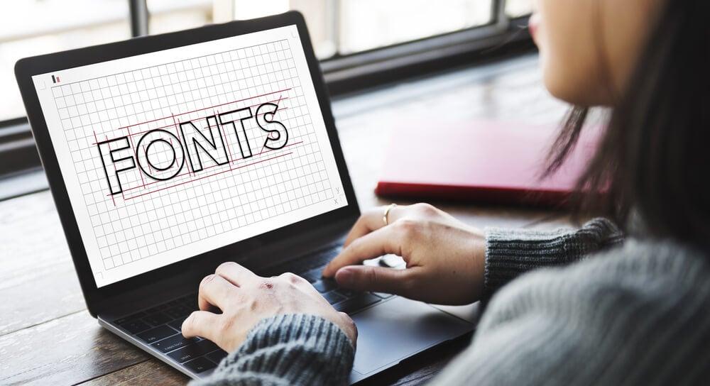 garota mexendo em laptop com conteúdo de fontes importante no processo de criação de identidade visual