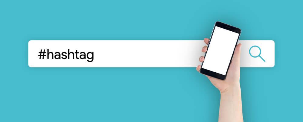 ilustraçao demonstrando a palavra hashtag em um campo de pesquisa com uma mao segurando um smartphone ao lado