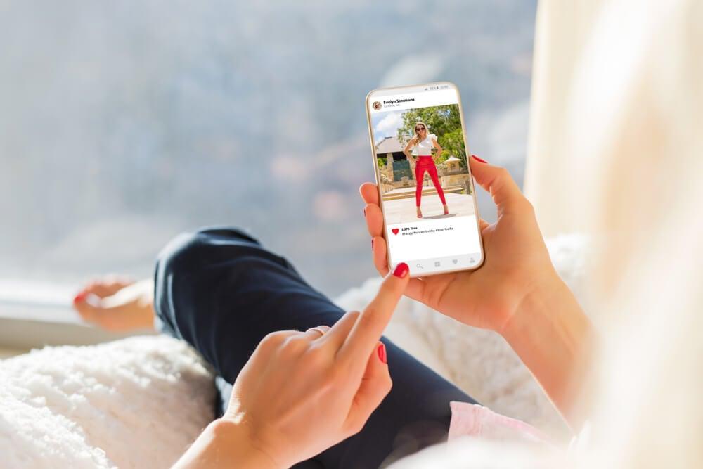 mao feminina segurando smartphone em postagem no aplicativo instagram