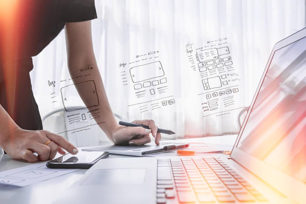 mão masculina em frente a laptop e ilustrações sobre identidade web de marca