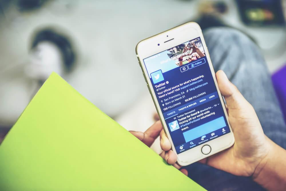 mao masculina segurando smartphone no aplicativo twitter
