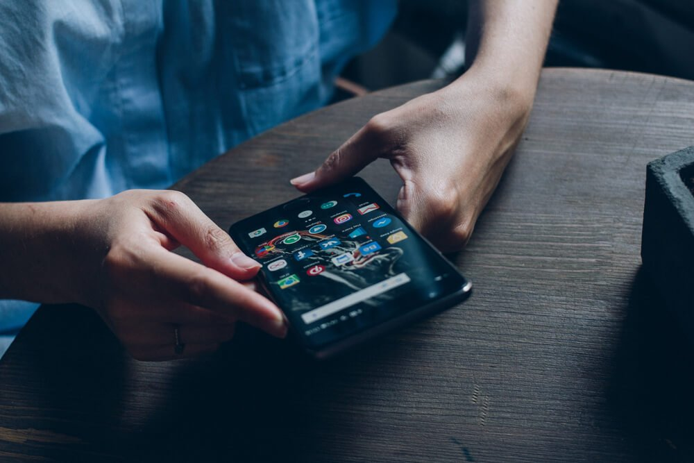 mãos femininas acessando smartphone