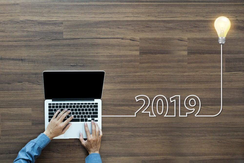 mesa executiva com laptop e ilustraçao de lampada com os numeros 2019
