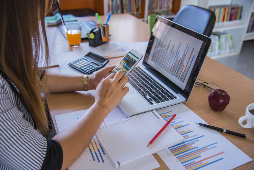 mulher sob mesa acessando smartphone em gerenciamento de redes sociais