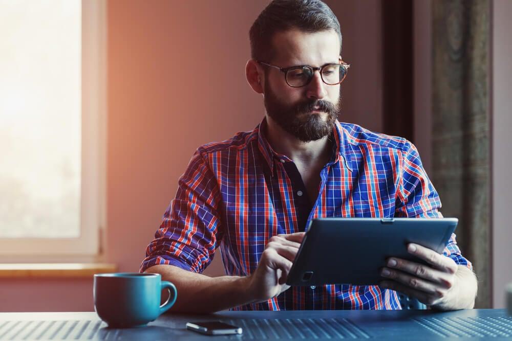 profissional trabalhando em tablet junto de caneca de café