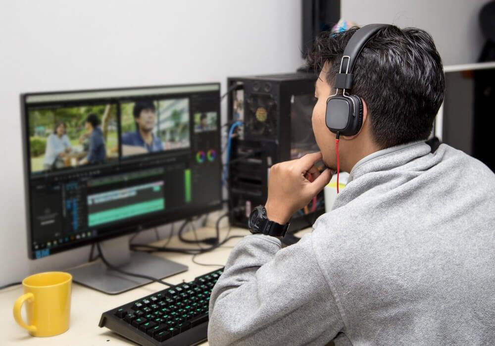homem em mesa de escritorio com fones de ouvido editando video em computador