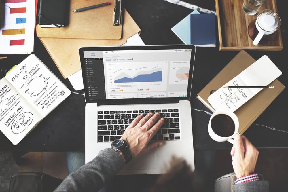 homem segurando xicara de cafe ao teclar em laptop sob mesa com materiais de escritorio