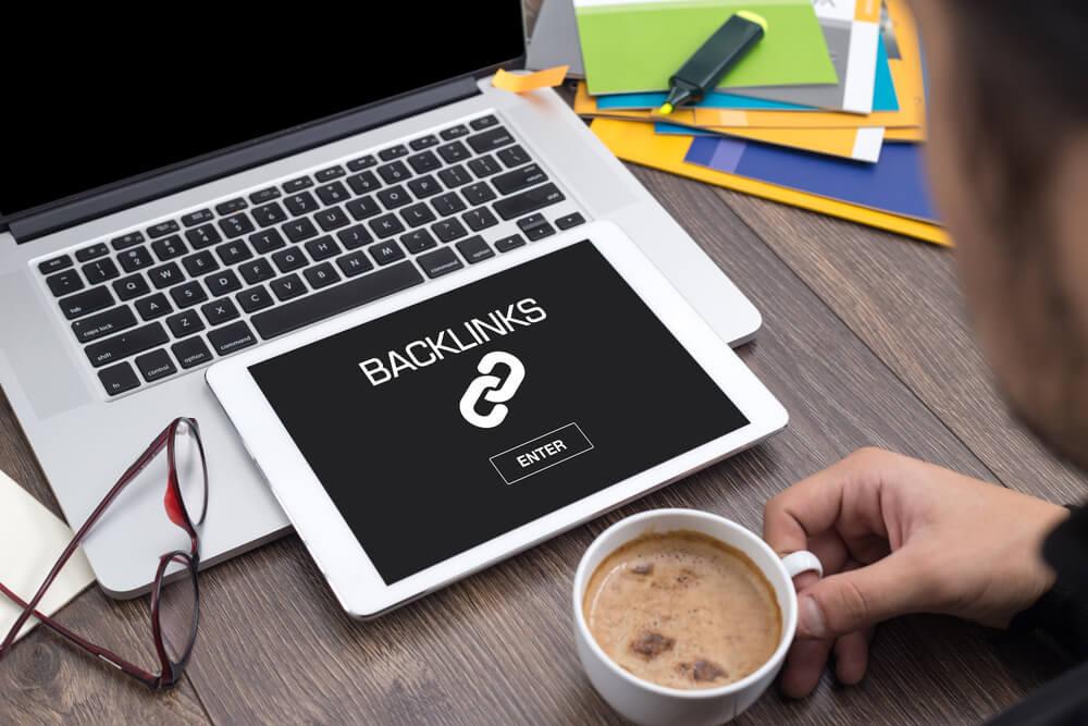homem segurando xicara de cafe em frente a laptop e tablet com a palavra backlinks em tela