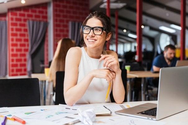 mulher em mesa de local publico em frente a computador