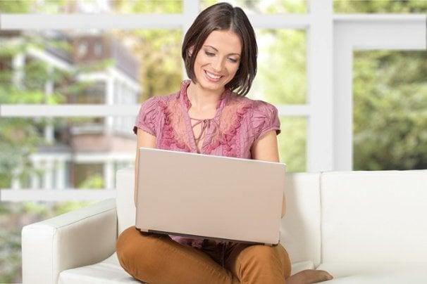 mulher sentada sorrindo ao olhar para tela de computador