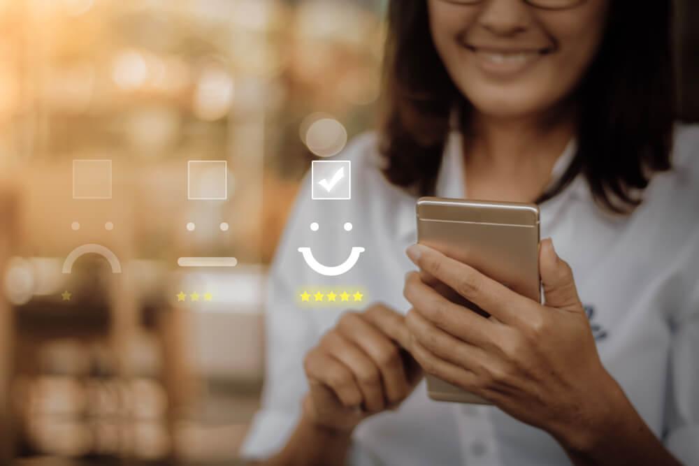 mulher sorrindo com smartphone em maos efetuando feedback de video