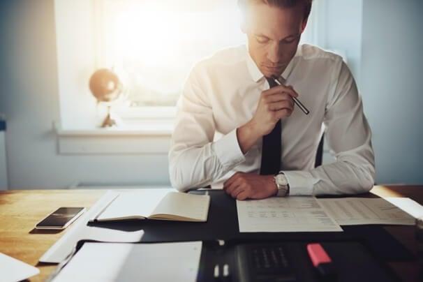 profissional executivo analisando dados e documentos em mesa de escritório