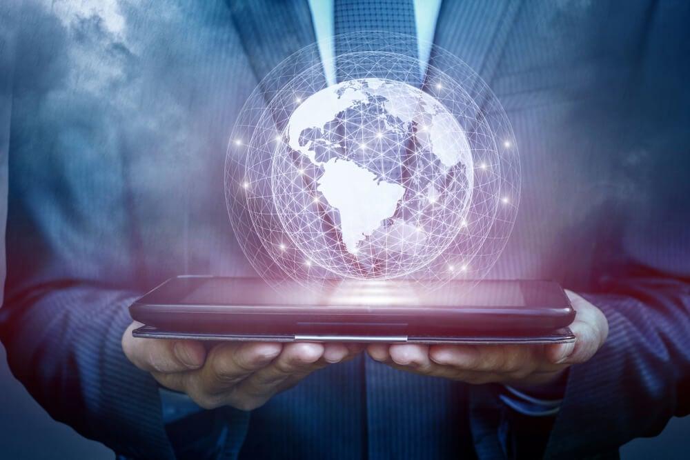 profissional segurando tablet com projeção de globo