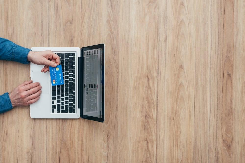 visão de cima de laptop e pessoa segurando cartão de crédito