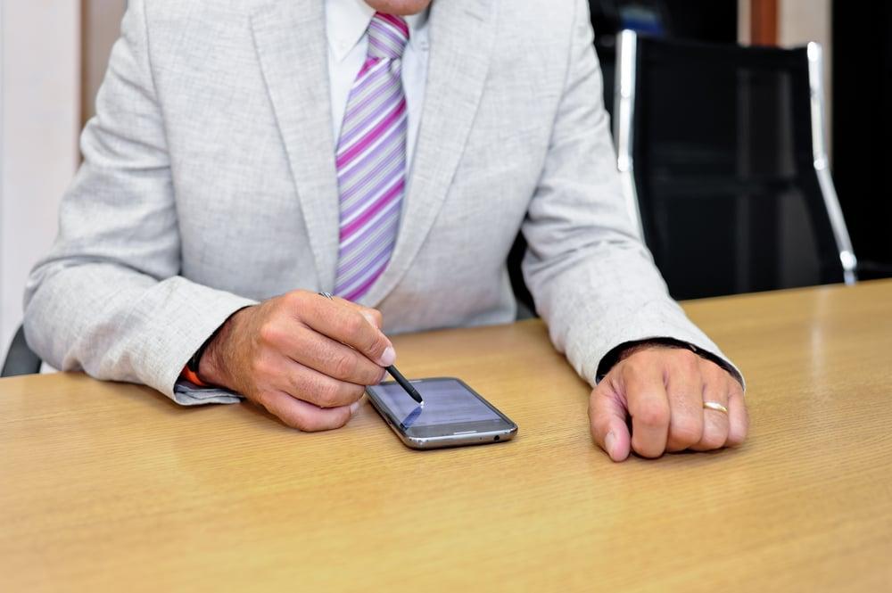 homem com celular na mao lendo emails
