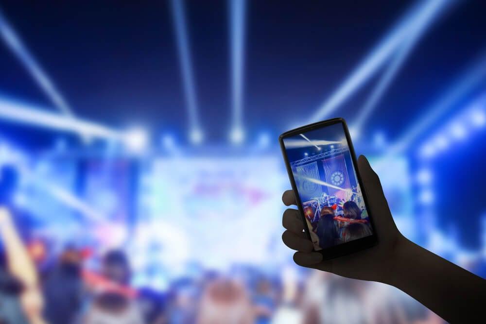 smartphone em transmissão de show musical pela ferramenta live do facebook