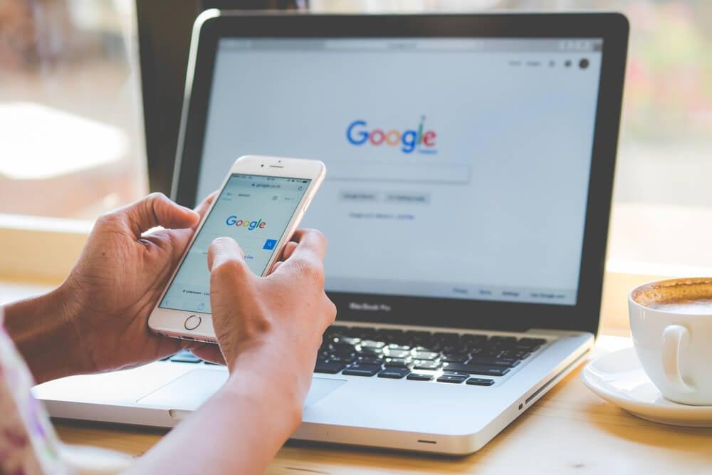 página inicial de busca do google em laptop e smartphone