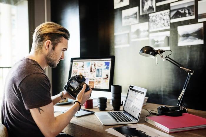 fotógrafo em frente ao laptop vendendo imagens