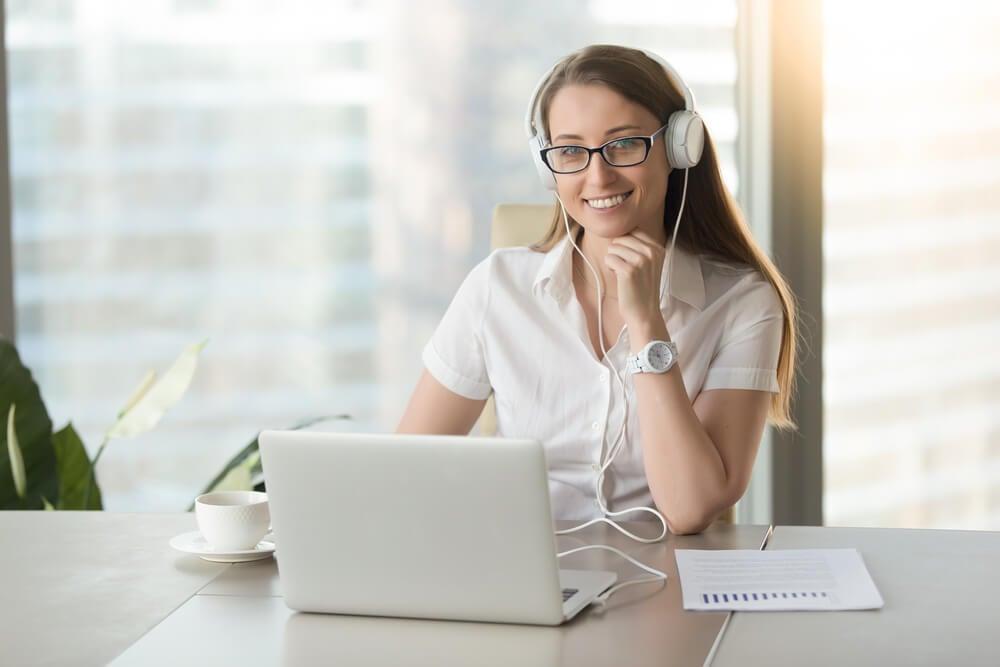 garota jovem trabalhando em seu laptop e de headphones
