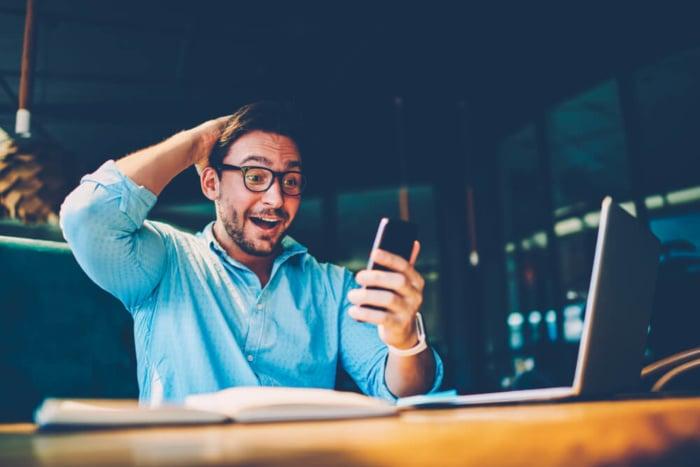 homem impressionado com ganho de dinheiro pelo smartphone