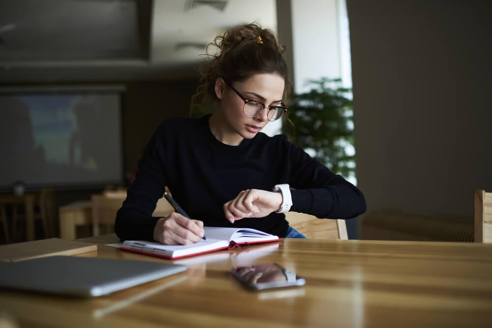 mulher jovem olhando ao relógio enquanto trabalha