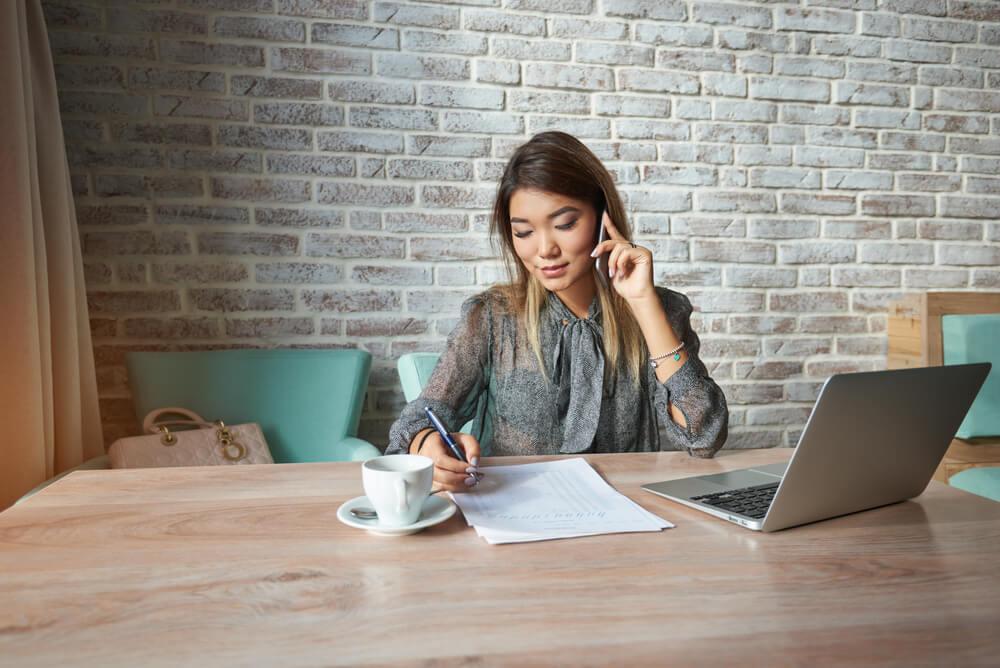 mulher perfil oriental ao telefone em meda de escritório