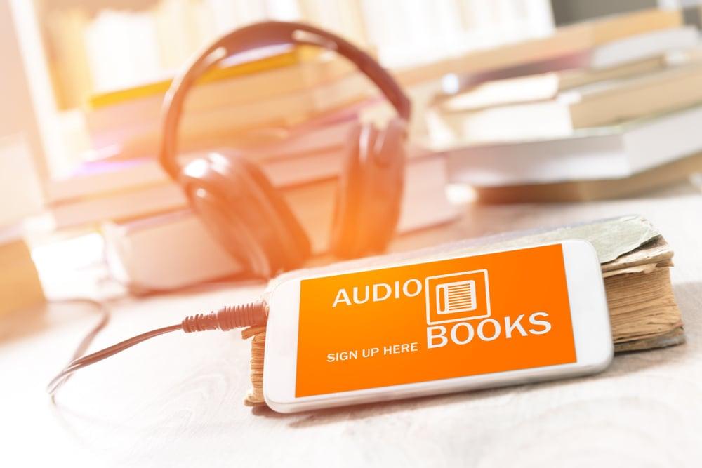 smartphone com acesso a um livro em audio e fone de ouvido