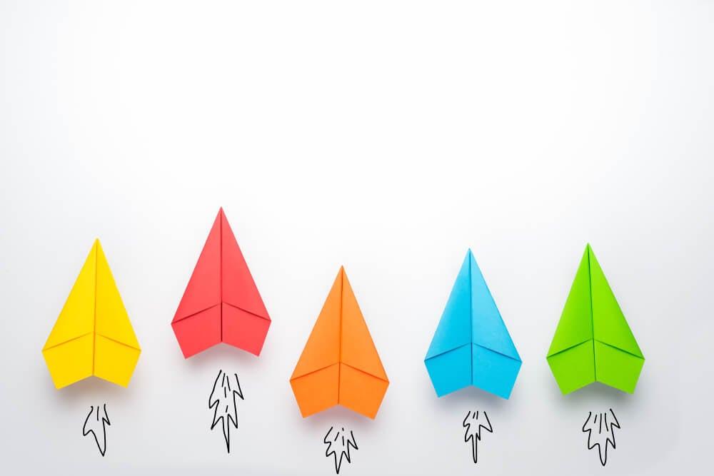 aviões de papel coloridos em fundo branco