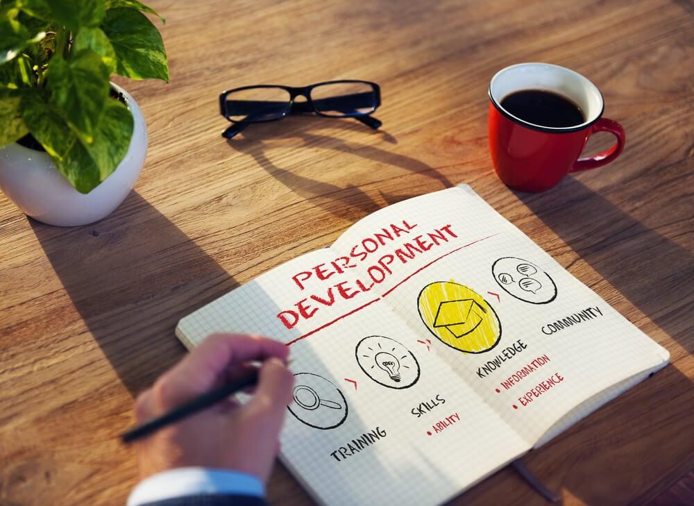 caderno com anotações sobre desenvolvimento pessoal e plata sobre mesa