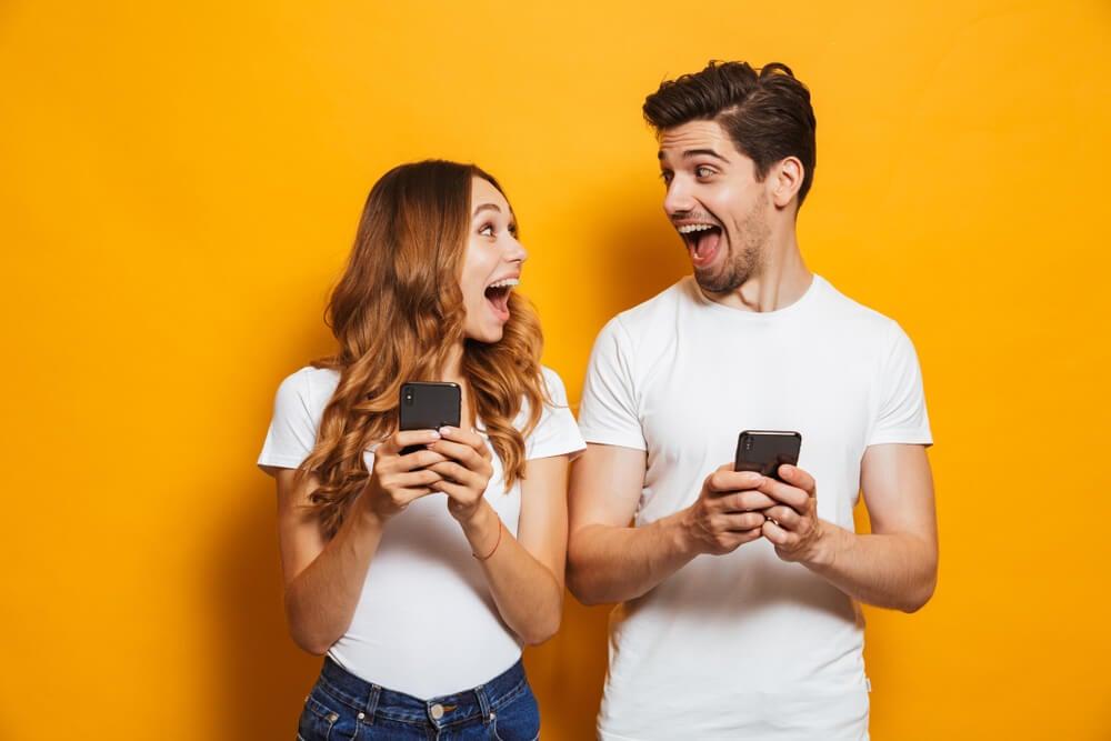 casal expressivo a frente de fundo amarelo segurando smartphones