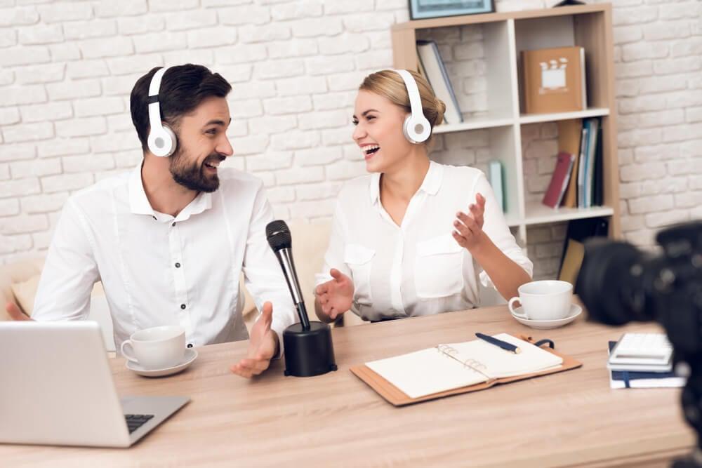 casal rindo com fones de ouvido falando em microfone